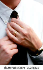 Hands of a married man straighten his tie in preparation for work, a date, a meeting, an interview, etc. (prominent display of wedding band, shallow focus point on hands).