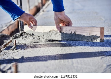 The hands of a mason using a piece of wood to level and move wet cement on a newly poured slab