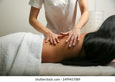hands of a massage therapist doing back massage of a woman