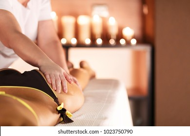 Hands of the massage therapist in the spa salon make massage to a young unidentified woman. Concept of care and beauty.massage of buttocks, prevention of cellulitis