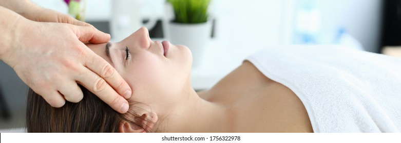 Hands massage whiskey to girl who lying on towel. Woman worried about insomnia, normalization sleep. Relieve muscle tension after heavy physical exertion or difficult day. Gentle caring hands master