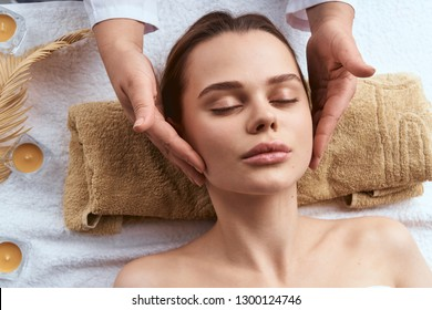hands massaging face of spa care woman