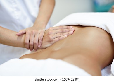 Hands massaging female abdomen.Therapist applying pressure on belly. Woman receiving massage at spa salon