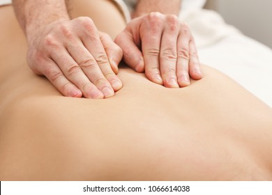 Hands massaging female back. Professional body treatment or relaxation procedure at spa salon. Health care, beauty and wellness concept.