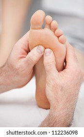 Hands massaging a foot on a medical table