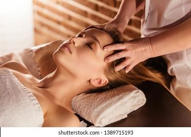 Die Hände der Masseuse machen eine manuelle Massage des Kopfes zu einer schönen Klientin. Konzept der Kopfhautbehandlung und Stimulation des Haarwuchses