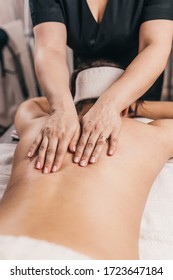 Hands of a masseuse on a female back during work - treatment of diseases of the back and spine - elimination of back muscle clamps