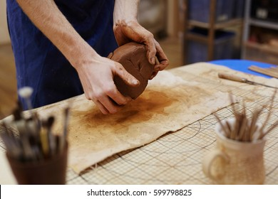 Hands of master kneading brown clay over workplace
