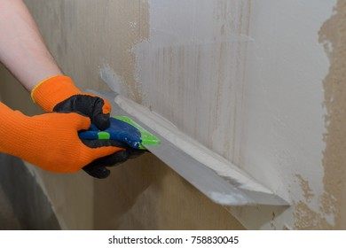 hands of master putty wall with white plaster putty