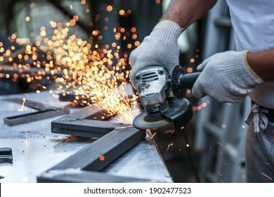 the hands of the master saw the metal with a grinder. metal works in the workshop close up