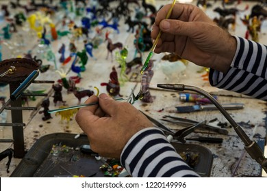 The hands of the master while working with a glass figure
