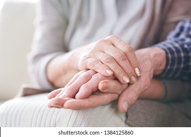 Hands of mature wife or carer holding that of her aged husband or patient as expression of care and support