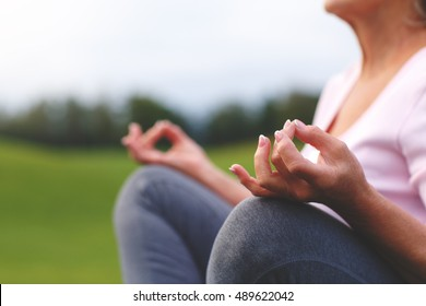 Hands of mature woman practicing yoga at lotus pose, outdoors