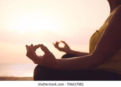 Hands of mature woman practicing yoga at lotus pose, at the sea beach