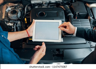 Hands of mechanic and customer using application on tablet computer when performing car diagnostic test