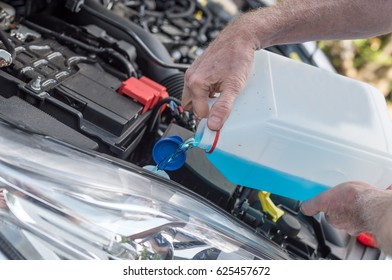 Hands of mechanic pouring windscreen washer in a car