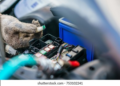 The hands of the mechanic replacing  fuse in car and selects the correct fuse. selective focus