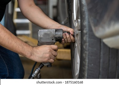Hands of mechanic using pneumatic wrench changing tyre of car at auto repair shop. Male mechanic changing, repair and maintenance wheel on car with electric drill to loosen the bolts