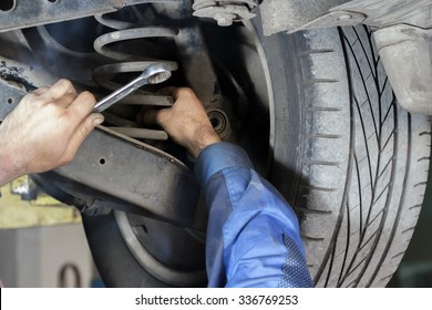 Hands mechanics to repair the suspension on the car