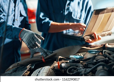 Hands of mechanics repairing car in auto service