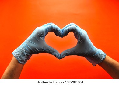 Hands in medical latex gloves. Hands form a heart shape. The gesture symbolizes the declaration of love. Red background. Close-up. Concept: Hand gestures for expressing emotions.