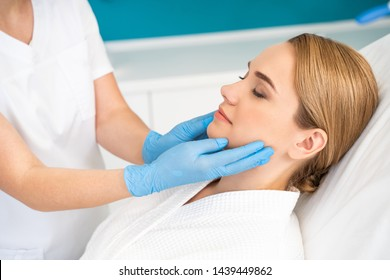 Hands of medical worker in rubber gloves touching the face of a young woman