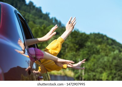 hands of men and children peering out of a car window on a background of mountains. Summer Road Trip.