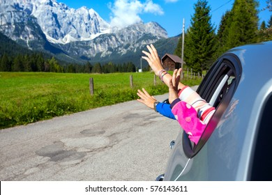 hands of men and children peering out of the car on a background of mountains.  Dolomites, Italy.