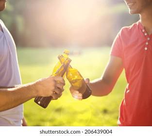 Hands of men clinking beer bottles in park