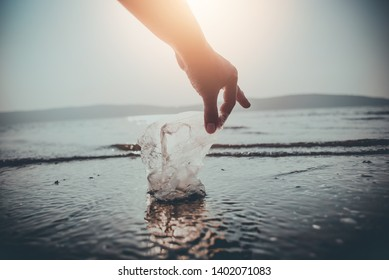 The hands of men are picking up plastic waste from the beach.