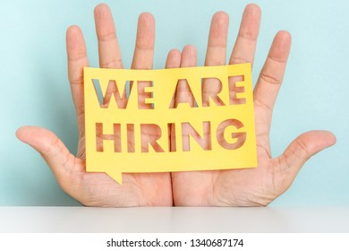 """Hands of a men showing a yellow banner with cutout phrase """"We are hiring"""". Employment concept."""