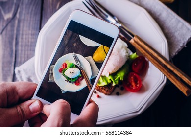 Hand's of men taking picture photo food with mobile smart phone. Top view