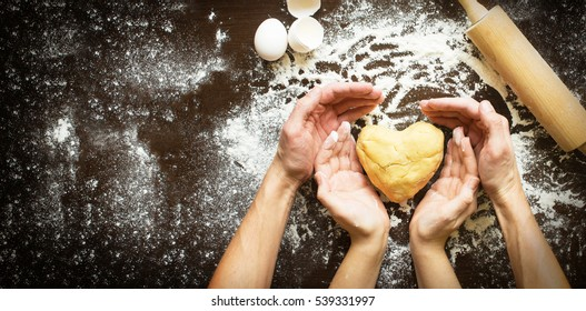 Hands of men and women make dough heart. The symbols of protection, warmth and comfort. Baking lovers on Valentine's Day