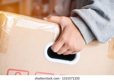 Hands messenger or deliveryman holding parcel box package to deliver customer. Delivery service courier, Detail for delivery man carrying cardboard with copy space. Online shipping  courier concept
