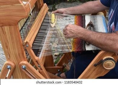 Hands of middle-aged man - craftsman weaver - working on wooden handloom, Etara ethnographic reserve, Bulgaria