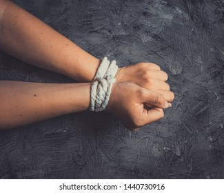 Hands of a missing kidnapped, abused, hostage, victim woman tied up with rope.