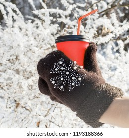 Hands in mittens hold hot drink, snowy weather hot tea