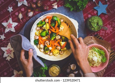 Hands mix baked roasted vegetables with spatula on Christmas lunch or dinner on red tablecloth. Vegan food with brussels sprouts, carrots, cauliflower, mushrooms. Social network trendy color style.
