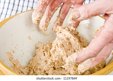 Hands mixing fresh dough in a bowl