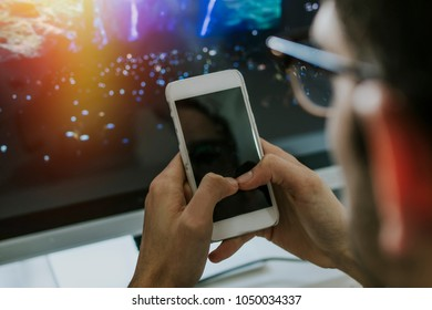 hands with the mobile phone on the desktop with the computer
