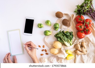 hands and mobile phone for searching online app for recipe , nutrition, diet and grocery shopping. - Shutterstock ID 1793573866