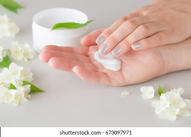 Hands moisturizing cream cares about woman's hands skin. Manicure beauty salon. Fresh jasmine flowers for fragrant atmosphere.