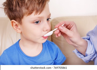 Hands of mom giving cough syrup medicine on spoon to sick son