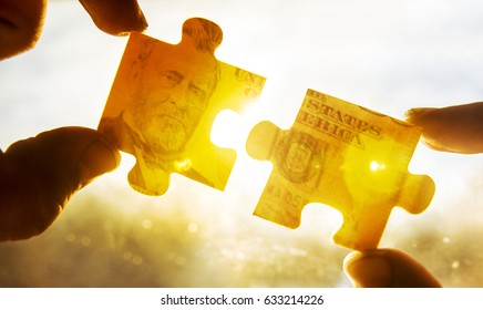 Hands and money puzzle  on sunny sky background. 50 fifty dollar bill made from two pieces of puzzle