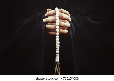 the hands of a monk with a rosary put together