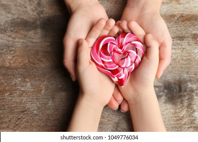 Hands of mother and child with heart-shaped candy on wooden background