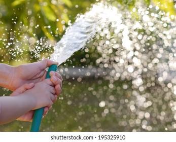 Hands of mother and child Help plants. watering plants in garden
