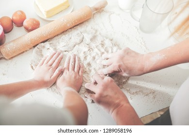 Hands of mother and daughter knead dough for pizza on white table. Having fun together in kitchen.Top view.