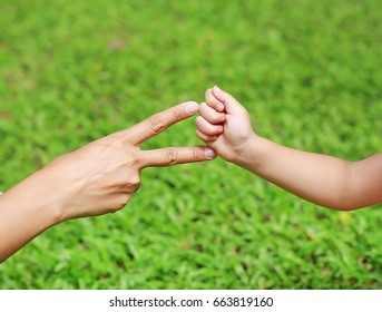 Hands of mother and daughter, Scissors and rock - hands on green grass background