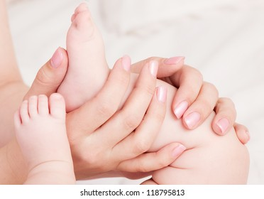 hands of a mother massaging her baby's feet, in bed at home